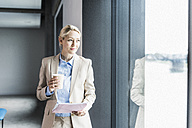 Businesswoman with coffee and documents at the window - UUF11390