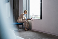 Businesswoman sitting at the window reading document - UUF11396