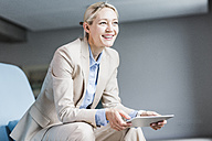 Smiling businesswoman holding tablet - UUF11402