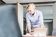 Businesswoman working at desk in office - UUF11411