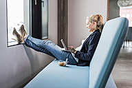Smiling businesswoman sitting on couch with feet up using tablet - UUF11420