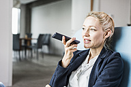 Businesswoman using cell phone sending voice mail - UUF11423