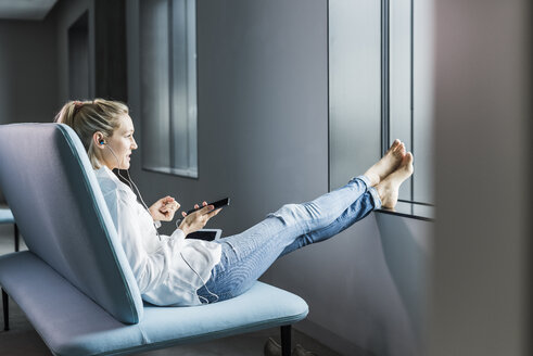 Businesswoman sitting on couch with feet up using cell phone - UUF11426