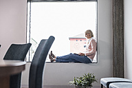 Businesswoman sitting on windowsill using tablet - UUF11441