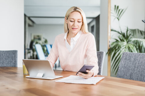 Businesswoman using cell phone and tablet in office - UUF11444