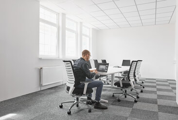 Businessman using laptop in conference room - RHF02012