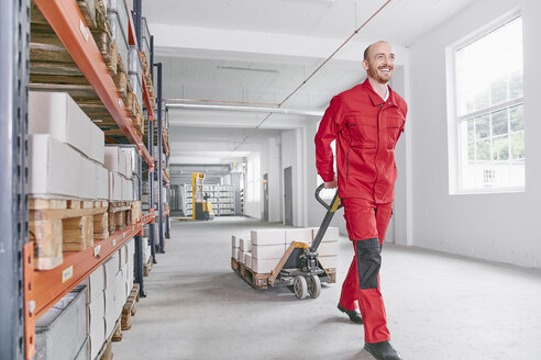 Smiling man in warehouse pulling pallet jack - RHF02024
