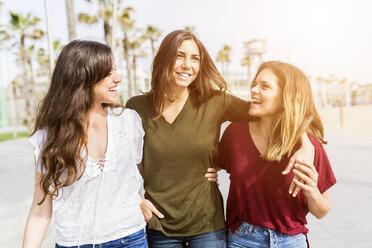 Three happy female friends strolling on the boardwalk - GIOF03002
