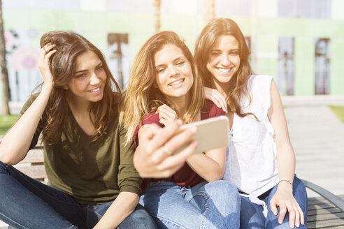 Three happy female friends taking a selfie outdoors - GIOF03005