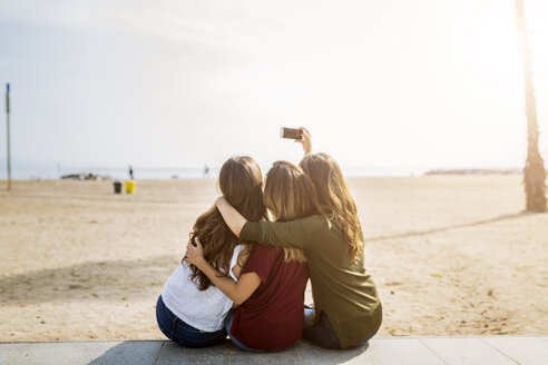 Rear view of three female friends sitting at the beach taking a selfie - GIOF03008
