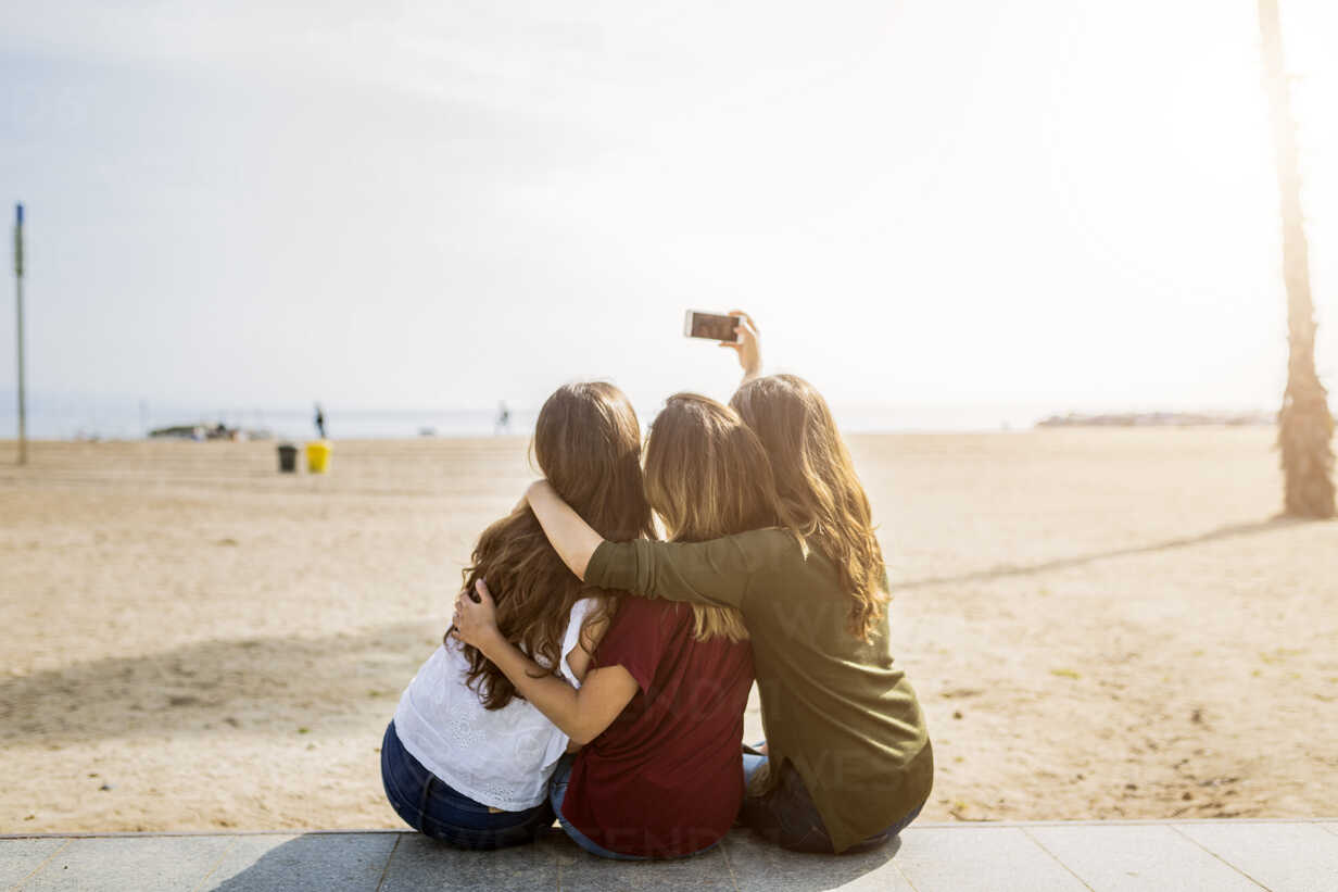 Rear view of three female friends sitting at the beach taking a selfie - GIOF03008 - Giorgio Fochesato/Westend61