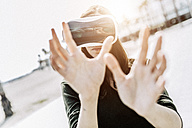 Young woman wearing VR glasses outdoors - GIOF03011