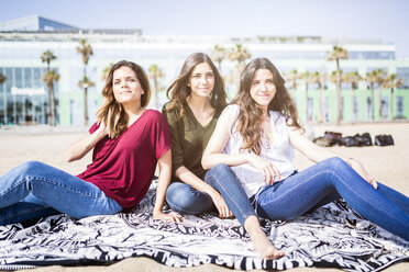 Three female friends relaxing on the beach - GIOF03014
