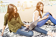Two young women using laptop and cell phone on the beach - GIOF03023