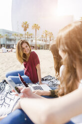 Three happy female friends using portable devices on the beach - GIOF03026