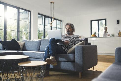 Senior man sitting on couch, using laptop - SBOF00457