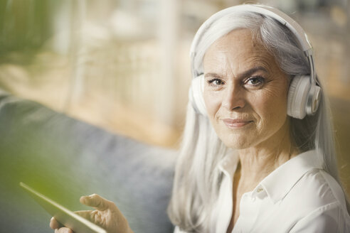senior woman using digital tablet and headphones - SBOF00478