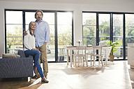 Senior couple standing in their comfortable loving room - SBOF00484