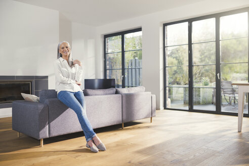 Senior woman standing by couch in living room - SBOF00487