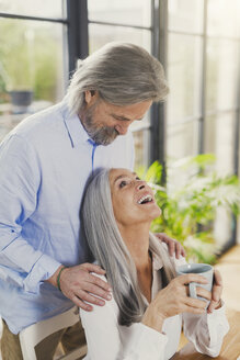 Happy senior couple drinking coffee at home - SBOF00493