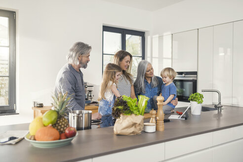 Grandparents with grandchildren and their mother standing in kitchen - SBOF00505