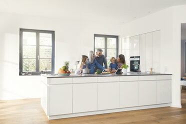 Happy family with grandparents and children standing in the kitchen - SBOF00508