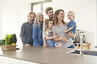 Happy family with grandparents and children standing in the kitchen - SBOF00517