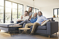 Senior couple with family sitting on couch - SBOF00520