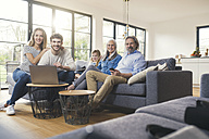 Extended family sitting on couch, using mobile devices - SBOF00523