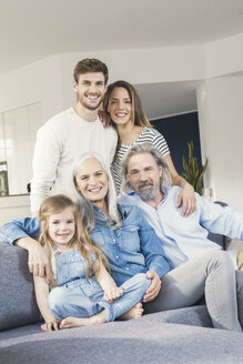 Extended family sitting on couch, smiling happily - SBOF00532