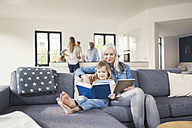 Grandmother and granddaughter sitting on couch, reading together book and tablet pc - SBOF00535