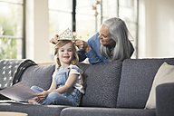 Grandmother playing with granddaughter, puuting crown on her head - SBOF00541