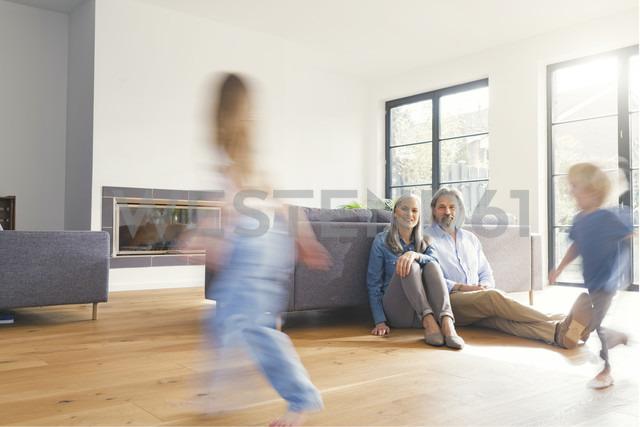 Grandparents observing grandchildren, playing in livingroom - SBOF00559