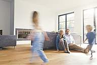 Grandparents observing grandchildren, playing in livingroom - SBOF00559