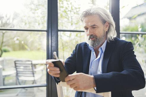 Senior businessman sitting on chair, using smartphone - SBOF00562