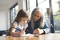 Grandmother and granddaughter making a drawing together - SBOF00571