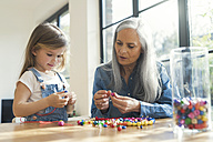 Grandmother and granddaughter threading beads - SBOF00574