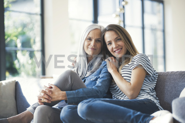 Daughter holding mother in her arms, sitting on couch - SBOF00580 - Steve Brookland/Westend61