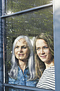 Mother and daughter looking out of window - SBOF00586
