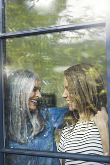 Mother and daughter looking out of window - SBOF00589