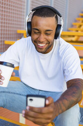 Laughing young man with headphones and coffee to go sitting on stairs looking at smartphone - MGIF00061
