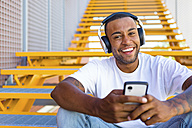 Portrait of laughing young man with headphones and smartphone sitting on stairs - MGIF00064