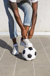 Young man tying his shoes on a soccer ball, partial view - MGIF00076