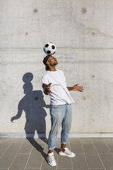 Young man balancing soccer ball on his head in front of concrete wall - MGIF00079
