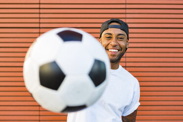Portrait of laughing man having fun with soccer ball - MGIF00082