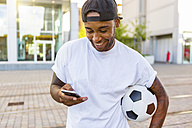Laughing young man with soccer ball looking at cell phone - MGIF00085