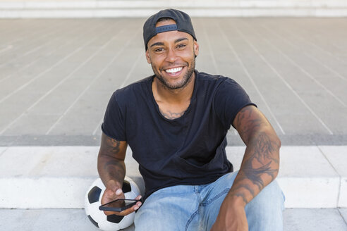 Portrait of laughing young man with smartphone - MGIF00091
