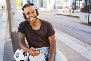 Portrait of smiling young man with soccer ball, headphones and cell phone waiting at tram stop - MGIF00094