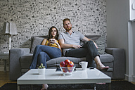 Young couple sitting on couch watching TV - MOMF00210