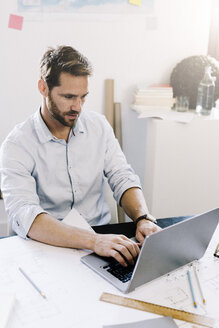 Architect working on laptop in his office - GIOF03045